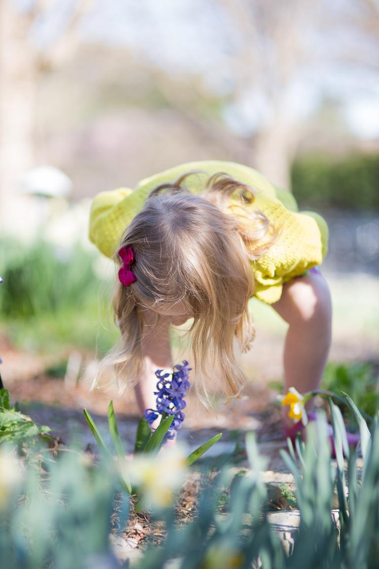 girl smelling flower at Botanica Wichita